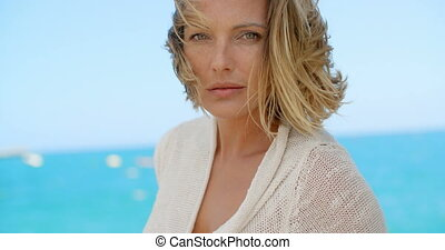 Blond Woman with Wind Swept Hair in front of Ocean