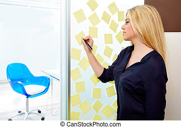 Blond young executive with stickers in office