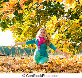 blond young girl drop up leaves in autumn color