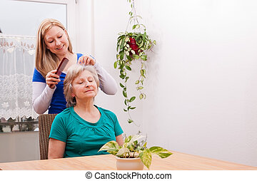 young woman combing seniors hair