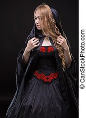 Blond young woman in black cloak