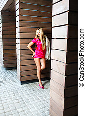 Blond young woman in pink dress posing