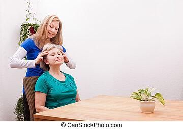 blond Young woman massaging female seniors scalp - pretty...