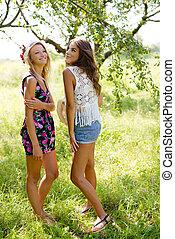 Blonde and brunette smiling girls standing in summer park