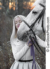 Blonde and white horse looking into each other's eyes