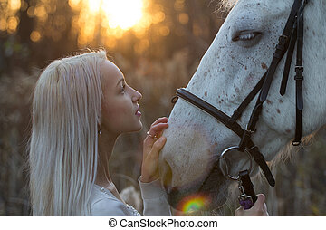 Blonde and white horse looking into