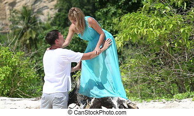 blonde asian girl standing on root of tree kisses man