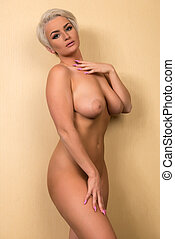 Blonde at a wall - Beautiful shapely blonde standing nude at...
