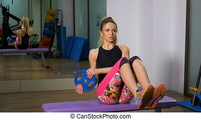 Blonde attractive woman doing abs exercise with light weight in hands