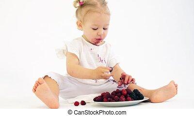 Blonde baby girl eating berries against white background -...