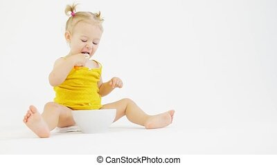 Blonde baby girl eats her breakfast on white background