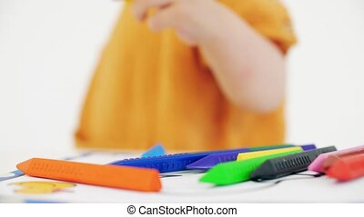 Blonde baby girl putting yellow crayon on the table