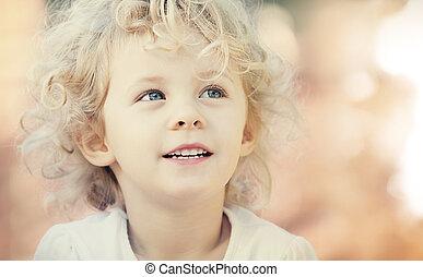 Blonde baby girl smiling outdoor. Closeup vintage portrait