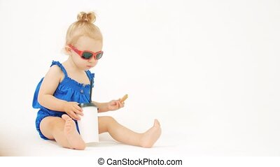 Blonde baby girl wearing sunglasses eats and drinks from...