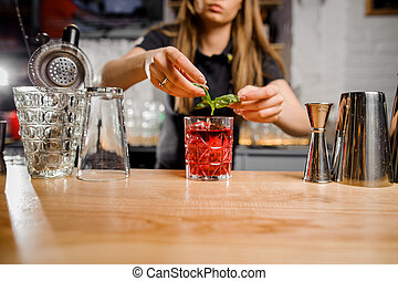 blonde barmaid adding to the cocktail mint leaves