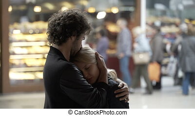 Blonde beautiful girl kissing hugging and talking with her boyfriend in public center using caressing and romantic gesture