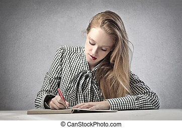 student writes - blonde beautiful student writes sitting at ...