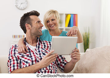 Blonde beautiful woman showing something on digital tablet