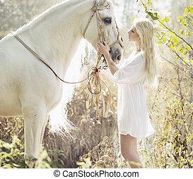 Blonde beautiful woman touching majestic horse