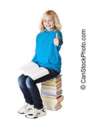 Blonde, beautiful young student sits on pile of books and shows thumb up.