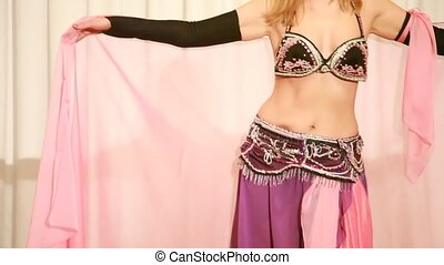 Blonde belly dancer in rose dress moves to the music,...