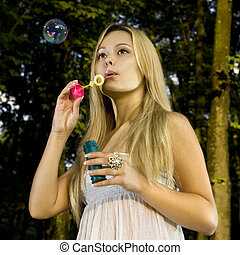 blonde blowing soap bubble - blonde young woman blowing soap...