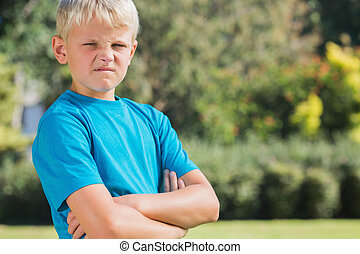 Blonde boy looking angry and frowning at camera in the park