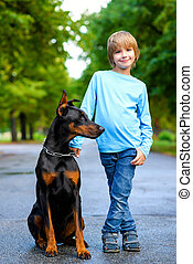 blonde boy posing with the dog or doberman in summer park