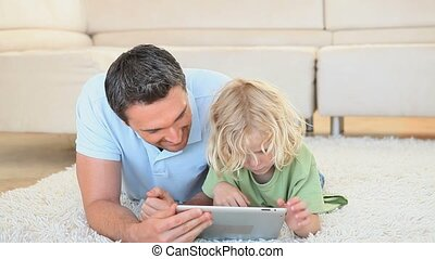 Blonde boy using a tablet computer with his father