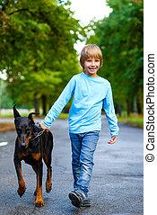 blonde boy walking with the dog or doberman in summer park