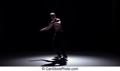Blonde breakdancer man doing handstand and dance breakdance on black, shadow, slow motion