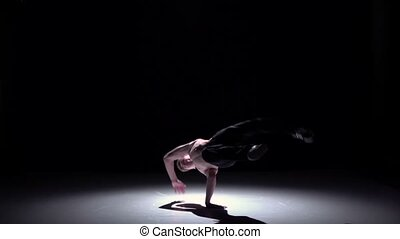 Blonde breakdancer man doing handstand on black, shadow, slow motion