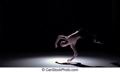 Blonde breakdancer man with doing handstand on black, shadow, slow motion