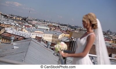 Blonde bride at the roof top in a city