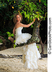 blonde bride in fluffy dress sits on tree trunk smiles