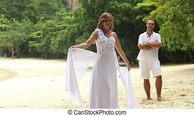 blonde bride in white wedding dress stand in front of young groom