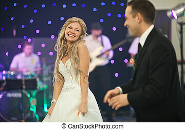 Blonde bride looks shy standing behind a groom in the dance hall