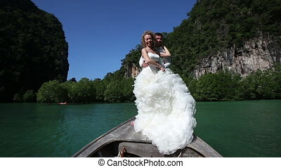 blonde bride poses and clasps to groom standing on longtail boat