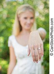 Blonde bride showing her diamond ring