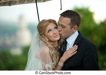 Blonde bride with big blue eyes looks up while groom kisses her cheek under an umbrella