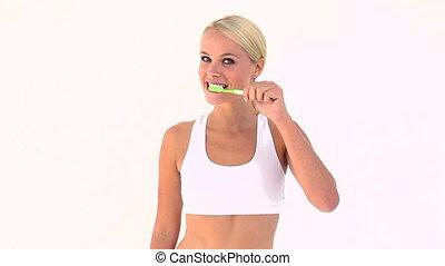 Blonde brushing her teeth
