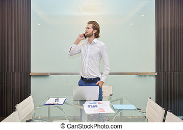 Blonde business man talking on the phone with blank glass board