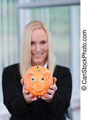 Blonde business woman with a piggy bank