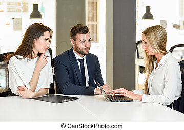 Blonde businesswoman explaining with laptop to smiling young couple.
