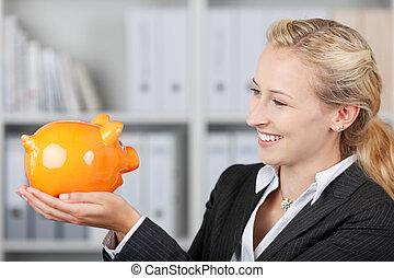 Blonde Businesswoman Holding A Piggy Bank