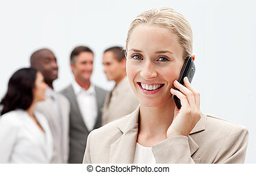 Blonde businesswoman on mobile with her team in the background