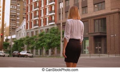 blonde businesswoman walks in town
