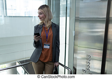 Blonde businesswoman with mobile phone standing in office elevator