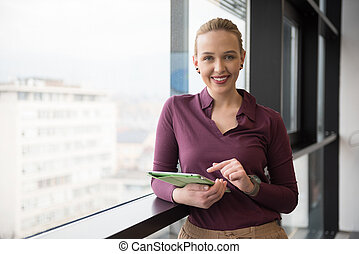 blonde businesswoman working on tablet at office