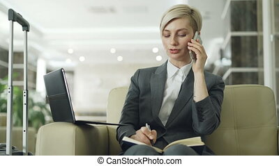 Blonde busy businesswoman sitting in armchair in hotel lobby talking mobile phone, writing in notepad and using laptop computer. Business, travel and people concept